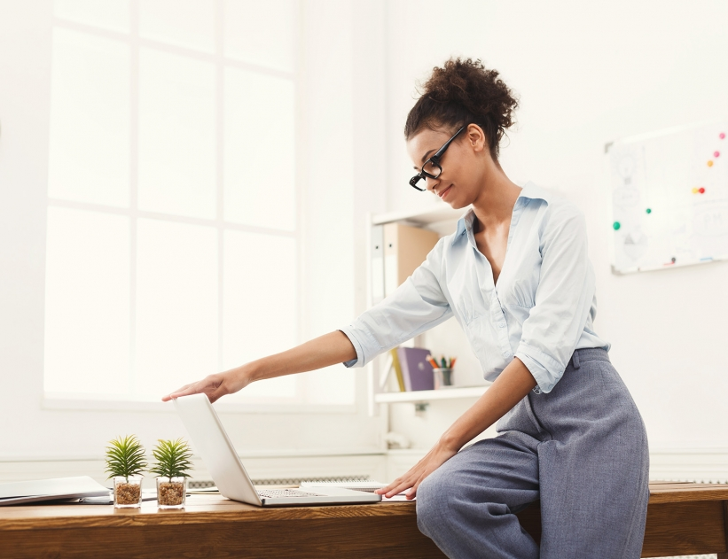 African-american businesswoman in modern office. Female worker opening laptop at office, copy space